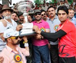 Skipper of combine Bhaderwah Sammer Malik receiving trophy from chief gust, Farooq Ahmed Khan, DDC Doda at Sports Stadium Doda on Monday.