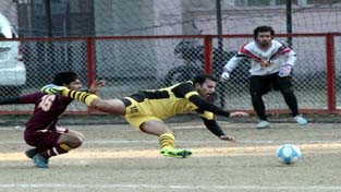 Footballer losing balance during a match of Christmas Soccer Championship in Jammu on Wednesday - Excelsior/Rakesh