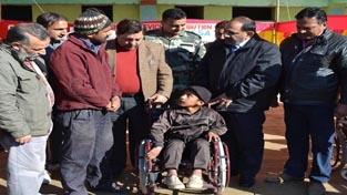 DDC Mubarak Singh distributing wheel chair to a beneficiary at Doda on Monday.