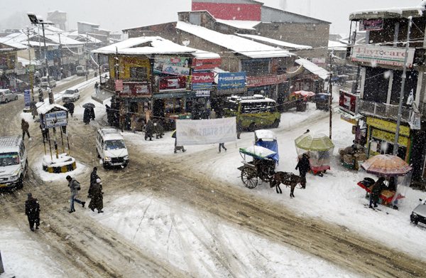 Life goes on amidst snowfall at Sopore on Tuesday. —Excelsior/Aabid Nabi