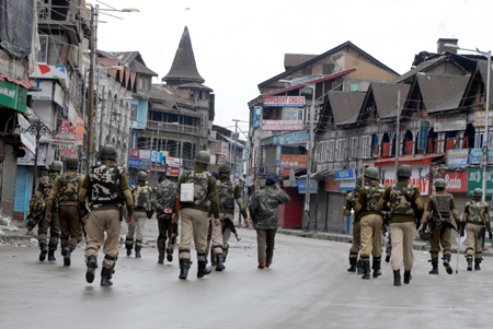 Paramilitary personnel patrolling a deserted street at Lal Chowk in Srinagar on Sunday. -Excelsior/Amin War