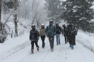 Tourists walk snow-covered area near famous Mughal Road connecting Poonch and Shopian on Monday. 	—Excelsior/Younis Khaliq