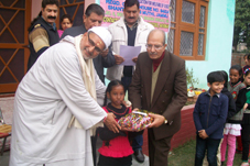 Swami Kumar Ji giving stationery items to a children at Barnai on Sunday.