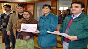 DDC Yasha Mudgal handing over relief cheque to a beneficiary at Udhampur on Saturday.