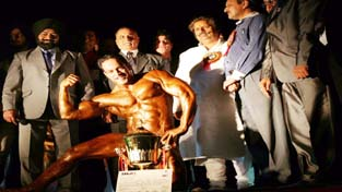 Body Builder displaying muscles while receiving a glittering