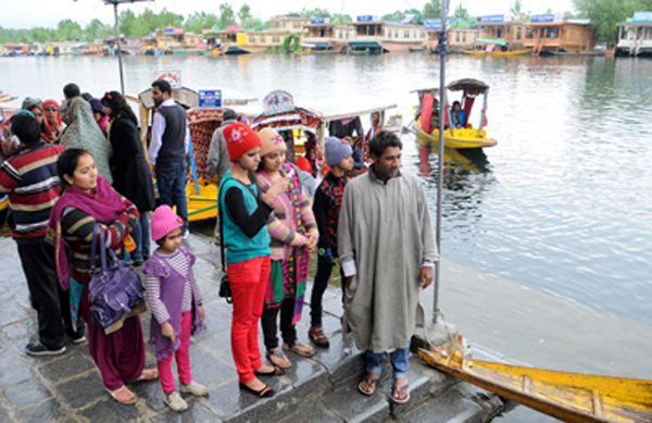 A group of tourists waits for a Shikara ride in the world famous Dal lake during a rainy day in Srinagar, on Wednesday. —Excelsior/Amin War