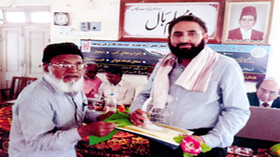Urdu writer, Dr Mushtaq Ahmed Wani receiving 'Waqaar-e-Adab' award from a dignitary at Malegaon in Maharashtra.