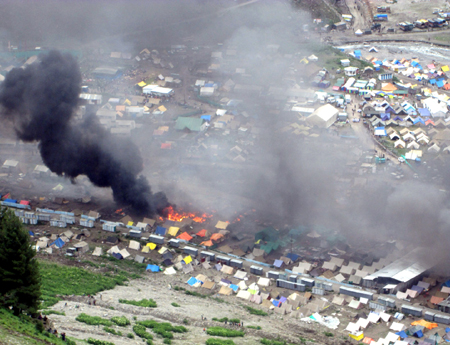 Smoke billowing out of langars and tents set on fire by miscreants at Baltal base camp on Friday.