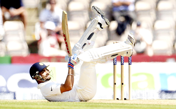 Virat Kohli rolls on the ground after avoiding a ball bowled by Chris Woakes during the third cricket test match at the Rose Bowl cricket ground, Southampton.