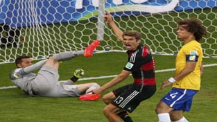 Germany's Thomas Mueller (C) celebrates past Brazil's David Luiz and goalkeeper Julio Cesar after scoring a goal during their 2014 World Cup semi-finals at the Mineirao stadium in Belo Horizonte.