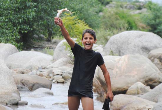 A boy enjoys fish hunt in Neeru river of Bhaderwah. (UNI)