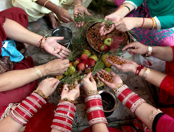 Women perform rituals for the long life of their sons on the occasion of Bacch Dua in Jammu on Thursday. —Excelsior/Rakesh