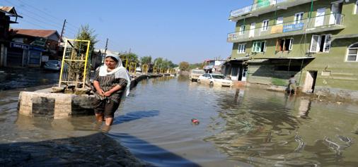 A woman walks in Jawahar Nagar locality of Srinagar on Sunday, which is still waterlogged. —Excelsior/Amin War