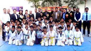 Young Taekwondo players posing along with dignitaries and officials during closing ceremony of Inter-School Taekwondo Championship in Jammu.