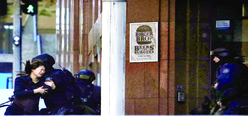 A hostage runs towards a police officer outside Lindt cafe in Martin Place in Central Sydney on Monday.(UNI)
