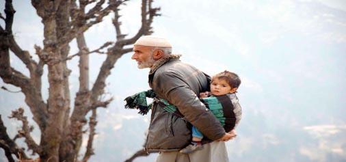 An elderly man carrying his grandchild making his way through rocky terrain towards home at Gundana village in Doda district on Saturday. (UNI)