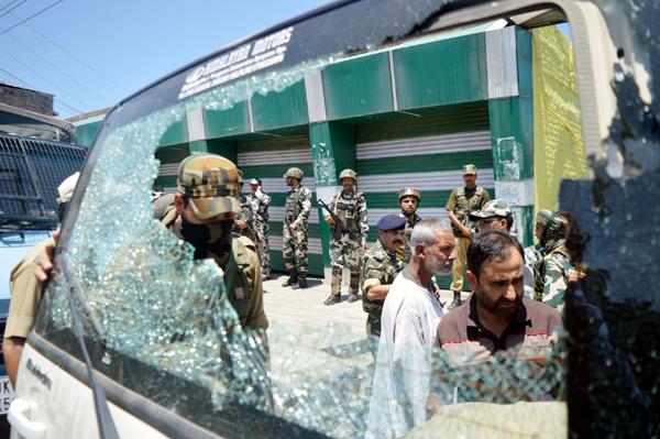 A vehicle damaged in grenade blast at Anantnag on Wednesday. — Excelsior/Sajad Dar