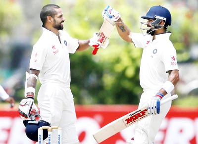 Shikhar Dhawan (L) celebrates his century with team captain Virat Kohli during the second day of first test cricket match against Sri Lanka in Galle on Thursday.(UNI)