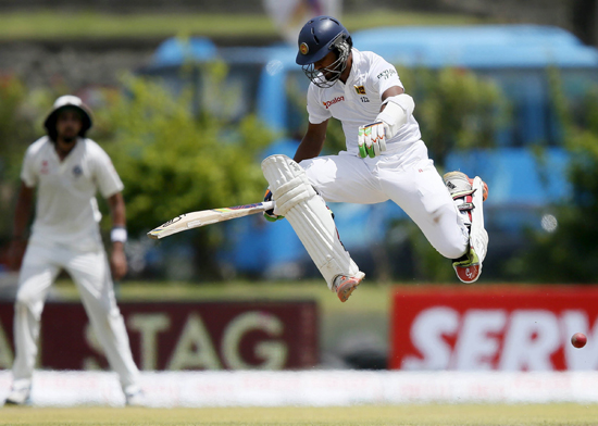 Sri Lanka's Dinesh Chandimal jumps over the ball as he avoids being run out during the first day of first test cricket match against India in Galle on Wednesday. (UNI)