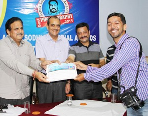 Excelsior Lensman Rakesh Bakshi receiving Ashok Sodhi Memorial Photography Award of PCJ at Jammu on Monday.