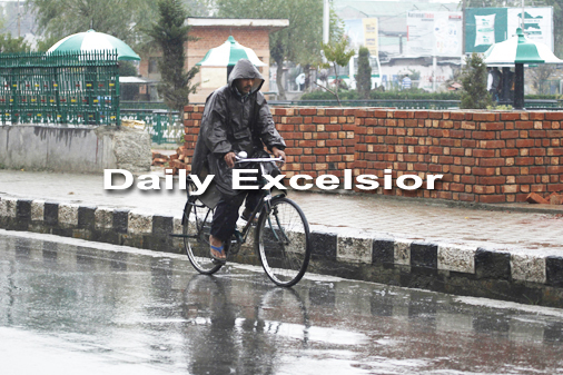 October-14,2015- SRINAGAR: A cyclist protects himself with his jacket as he drives in the rain at Residency Road in Srinagar, on Wednesday . Heavy rainfall in the Kashmir valley from early morning .Photo/Mohd Amin War
