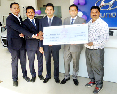 Hyundai representative Abhinav & dealer Rajinder handing over 'Gold Offer' cheque to winner Kishore Kumar at Mandi in Himachal.