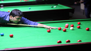 Cueist aiming a shot during a match of State Senior Snooker Championship at Billiards Hall, MA Stadium in Jammu. –Excelsior/Rakesh