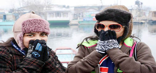 Tourists dressed in warm clothes sitting on the banks of famous Dal lake in Srinagar braving intense cold that gripped the Kashmir valley throwing the normal life out of gear on Saturday. (UNI)