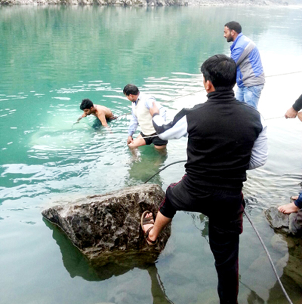 People recovering vehicle from river Chenab in district Ramban. -Excelsior/Pervaiz