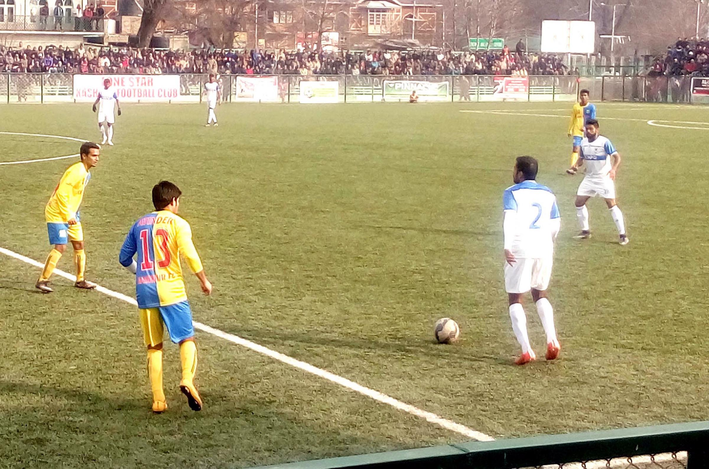 Footballers in action during a match between Lone Star KFC and Dempo Sports Goa at Synthetic Football Turf in Srinagar.
