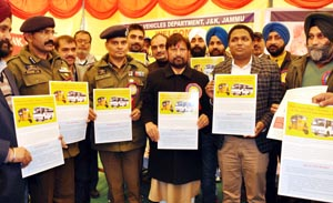 MLA Basohli Ch Lal Singh and others displaying posters on traffic rules at Jammu on Thursday.