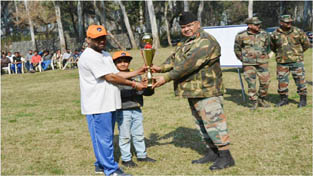 Army officer presenting Trophy to winner during a match of cricket tournament at Khour.
