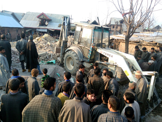 People gather at the site of grenade blast at Hajin, Bandipora on Sunday.