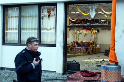 A police officers stand passes by a Gurudwara after three people have been injured in an apparently deliberate explosion.