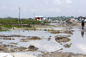 A view of Rakh-e-Arth under rainy water of Bemina on the outskirts of Srinagar on Friday. —Excelsior Photo