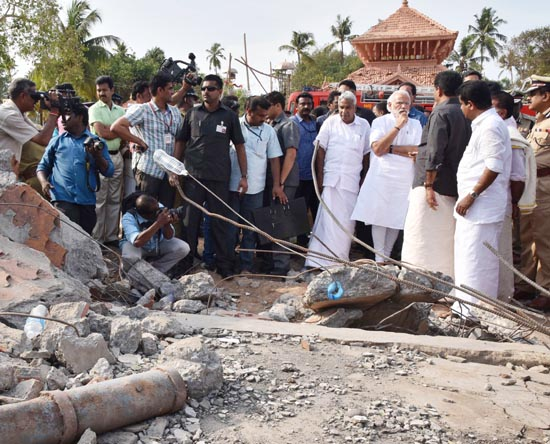 Prime Minister Narendra Modi and Chief Minister of Kerala Oommen Chandy take stock of the situation at Puttingal temple, Paravur, in Kollam, Kerala on Sunday. (UNI)