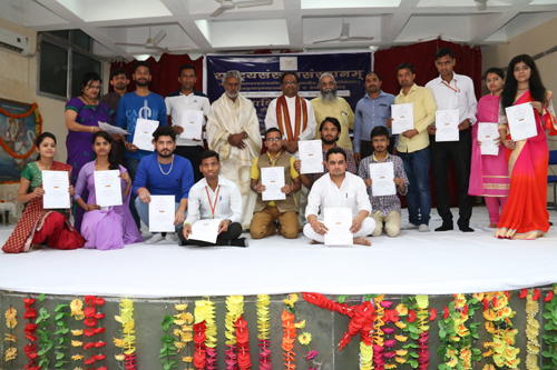 Students displaying certificates while posing for a group photograph during Annual Day celebration at Rashtriya Sanrkrit Sansthan.