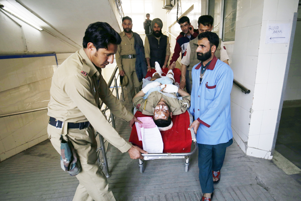 Cops and paramedics carry a policeman injured in grenade attack for treatment at a local hospital in Srinagar on Friday. — Excelsior Photo
