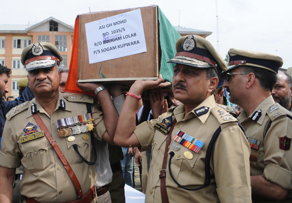 Director General of Police K. Rajendra Kumar with senior  police officers carry a coffin containing the body of slain policeman during the wreath laying ceremony of three policemen at Police Control Room in Srinagar on Monday. Excelsior Photo