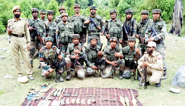 Security personnel posing for photograph with cache of arms and ammunition recovered from Khangar forest in district Rajouri.