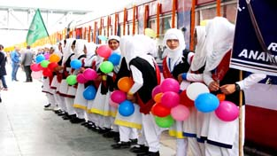 Girl students welcome new train at Anantnag on Thursday.