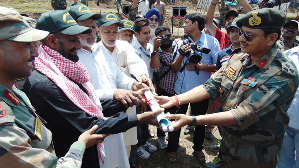 An Army officer submits papers to civilians, whose land was restored after de-mining in Nowshera sector on Thursday.