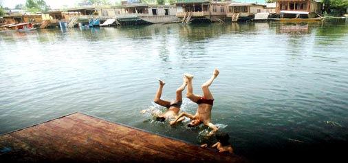 Kids beat summer heat by taking a bath in the waters of Dal lake in Srinagar on Sunday. (UNI)