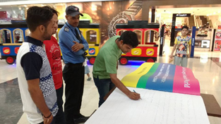 A person writing his message on largest notebook created by Vickrant Mahajan at Wave Mall, Jammu.
