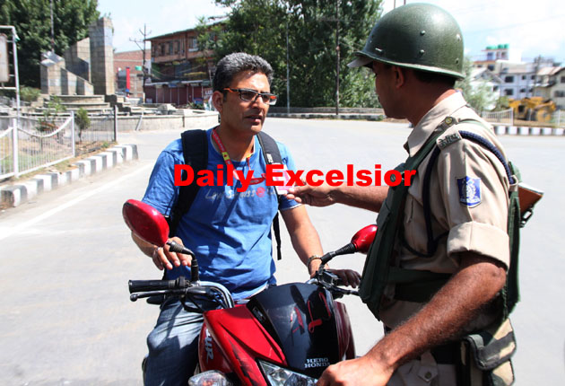 A paramilitary CRPF personnel checks identity card of a motorist during curfew in Munawarabad area of SrinagarExcelsior\Shakeel-ul-Rehman.