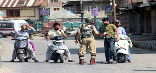 A security jawan stops two-wheeler operators during curfew in Srinagar on Monday. -Excelsior/Shakeel