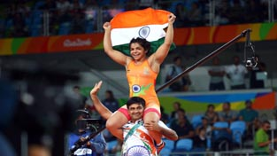 Sakshi Malik of India celebrates with her coach after winning the bronze medal in Women's Freestyle 58 kg.