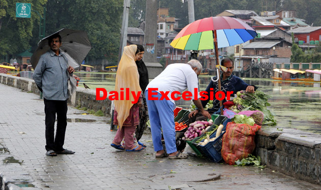 A Vegetable vendor sells Vegetables under umbrella during rain on the banks of Dal Lake on sunday.Excelsior\Shakeel ul Rehman
