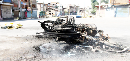 Wreckage of a motorcycle lying on road after protesters torched it at Batmaloo in Srinagar on Tuesday. -Excelsior/Shakeel