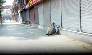 An elderly person sitting outside the closed shops at Abiguzar Market in Srinagar on Tuesday. (UNI)